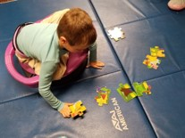 This photo shows a young boy sitting cross legged on a Dizzy Disk, pushing with his arms to reach and assemble a floor puzzle