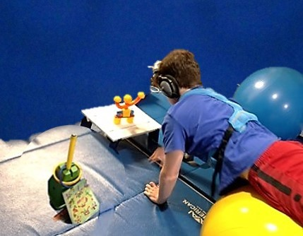 This photo shows an older boy walking out on a physioroll to collect and build a magnetic robot.