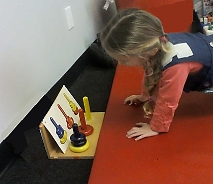 This photo shows a young girl using a  walk out to select and stack alternating color size  rings onto colored poles as shown by a task card.