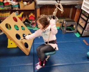 This young girl is holding the rope of a swing to pull the weight of her body up against gravity while she swings forward to toss a toy into a hole.