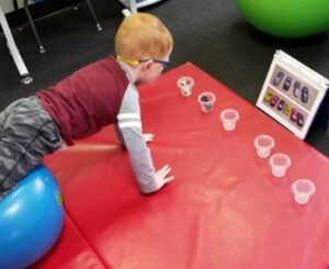 This young boy is pushing himself up against gravity on the Physioball  while he picks up and places each car into place as shown by the photo lineup.