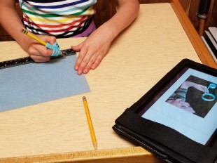 The photo shows a youngster tracing a line along the edge of a ruler that is positioned at the bottom of a piece of construction paper.  One hand is holding the paper still while the other hand is holding the pencil and drawing the line needed.