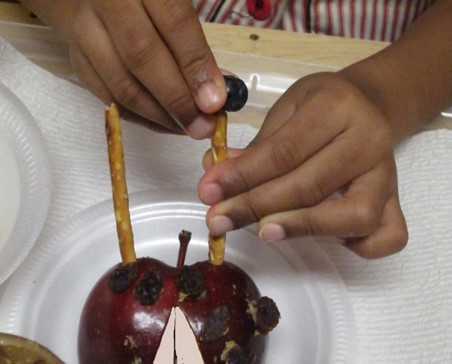 "the photo shows a girl making a food craft.  She is using an apple that has been cut in half while a  pretzel has been pushed into the front as antenna for a ladybug. The photo shows her using one hand to hold a pretzel stick still with one hand, while using the other hand to push a blueberry on top of the bugs'  ""antenna"""