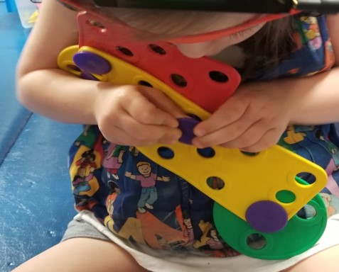 This youngster is also learning to use both hands working together while building a toy with Busy Buttons.  As she holds one part of the toy still with one hand, the other hand is busy pushing and twisting the button into place.