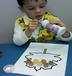 The photo above shows a boy manipulating  his fingertips with a paint brush.  He is twisting the brush to scrape the glue that he needs out of a bottle so he can continue his craft project.