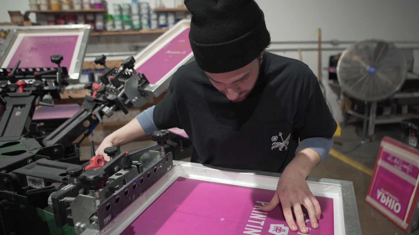 Man is looking down and focusing as he registers a screen on a manual screen printing press.