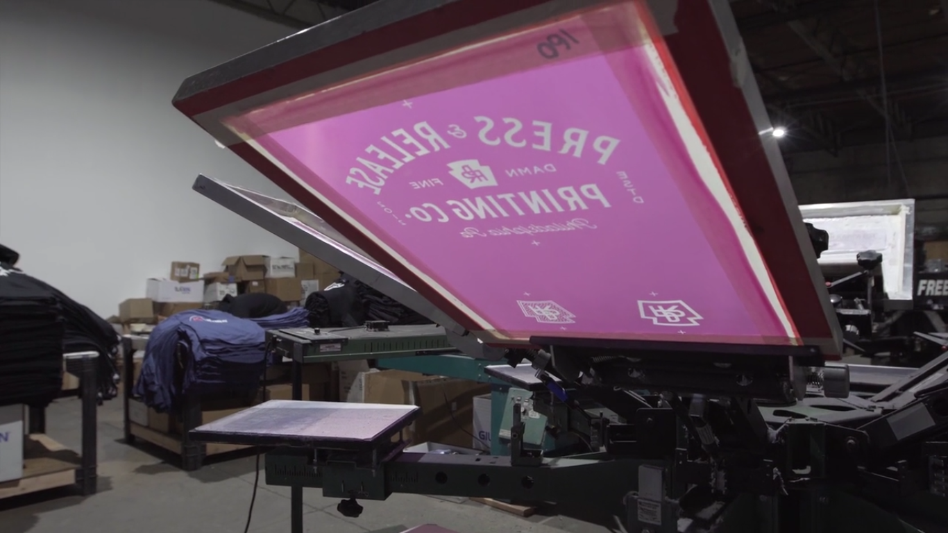 A manual screen printing press. The Press & Release Printing logo is burned into the screen.