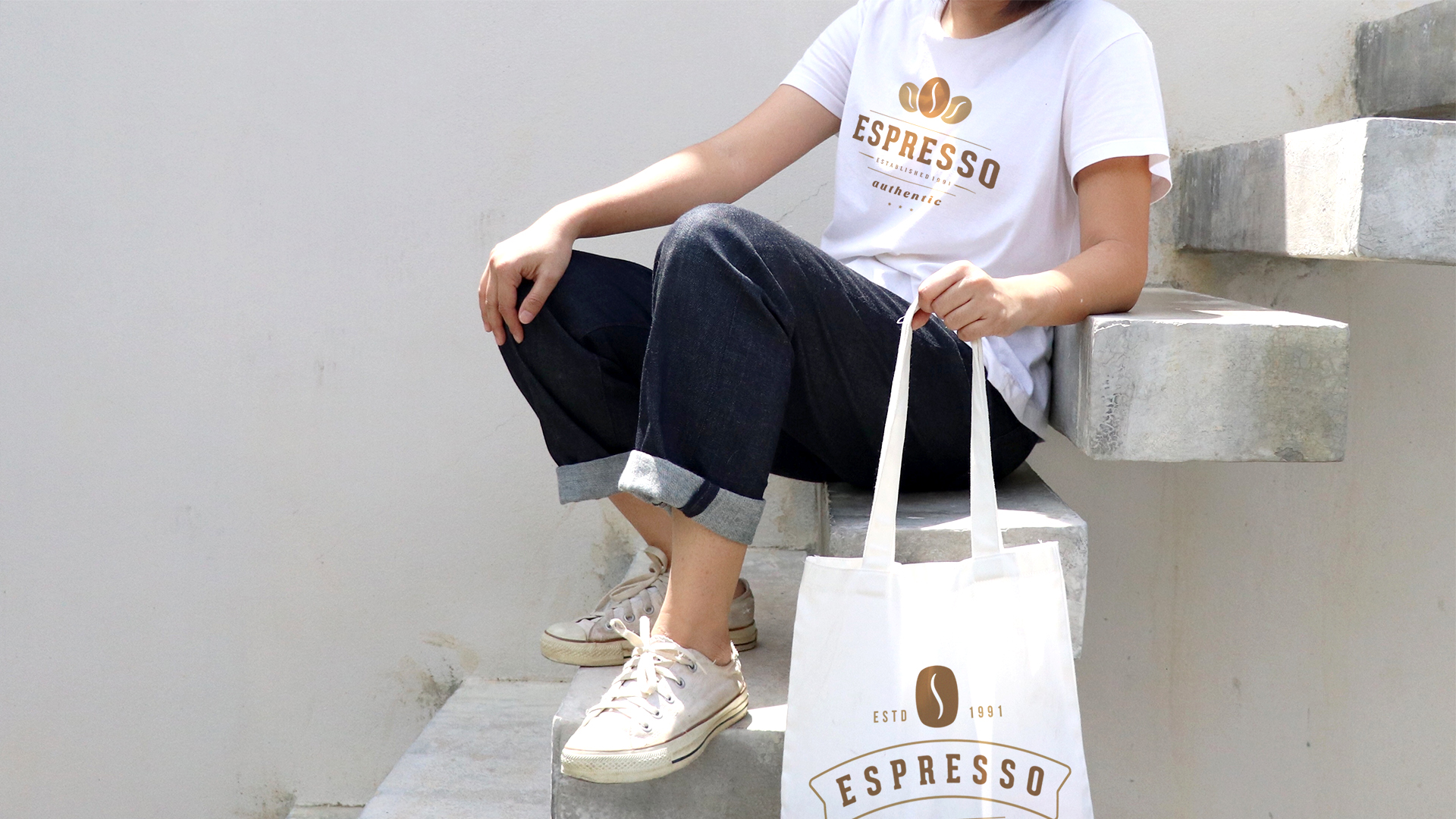 A person sits on some steps, wearing a screen printed t-shirt and holding a screen printed tote bag. Both items display a coffee shop logo, a great example of custom merchandise.
