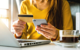 A woman sits at her computer with her phone and credit card in hand, ready to make a purchase online.