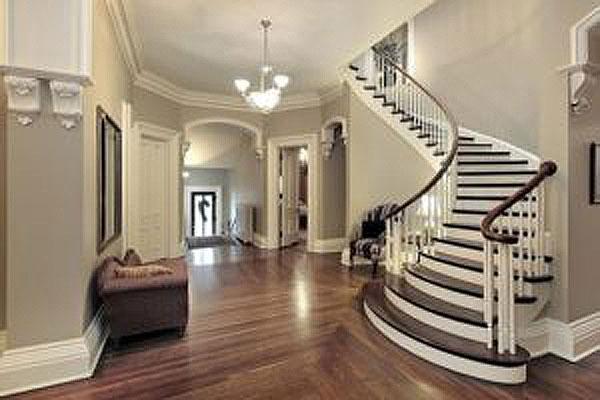 Grey-beige interior with dark wooden staircase steps and wooden floor