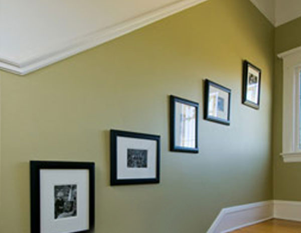 green hallway wall with 5 paintings stacked upwards