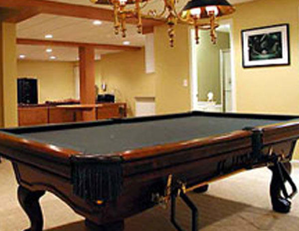 remodeled room with pool table and chandelier