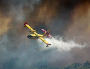 A yellow plane dropping water on a wildfire. Firefighters are at great risk of dehydration and may need to supplement with natural electrolytes.