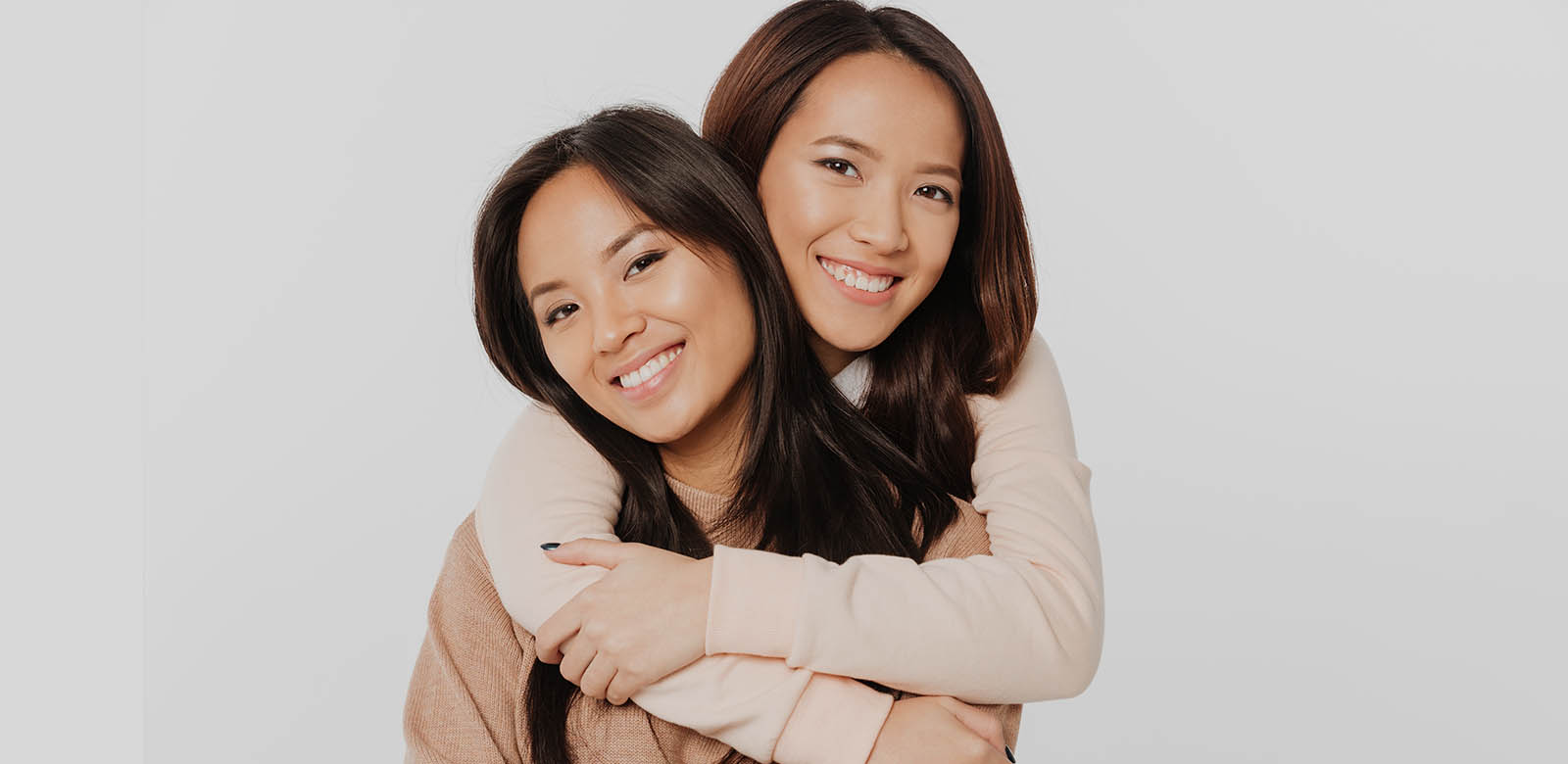 two asian women hugging and smiling