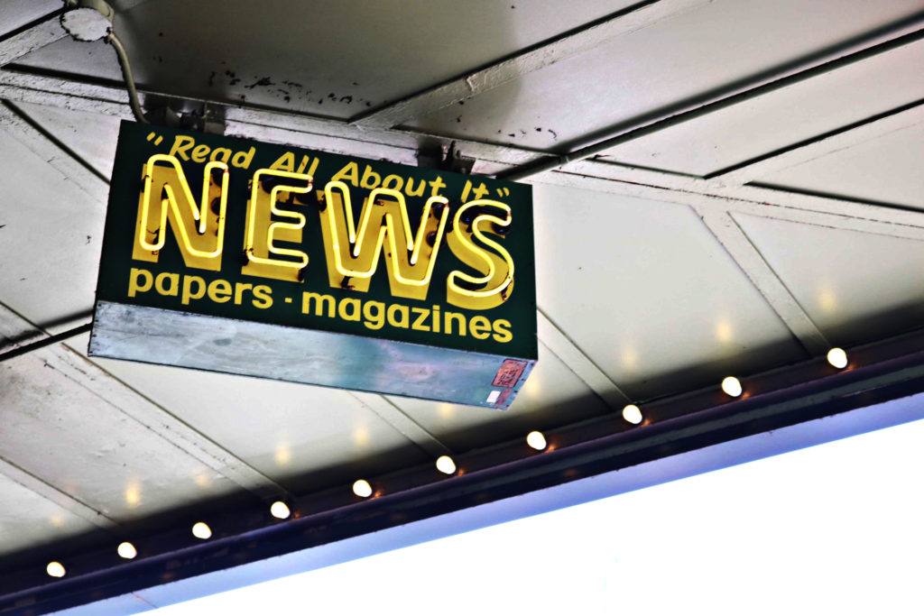 """Neon sign that reads """"Real All About it: News papers magazines"""" -- Build a public relations marketing strategy that will get you maximum media coverage."""