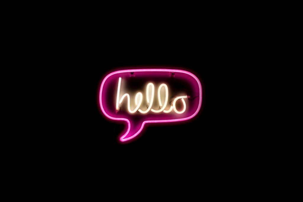 Zoom customer experience strategy is helping them crush financials in 2020: image of neon hello in speech bubble