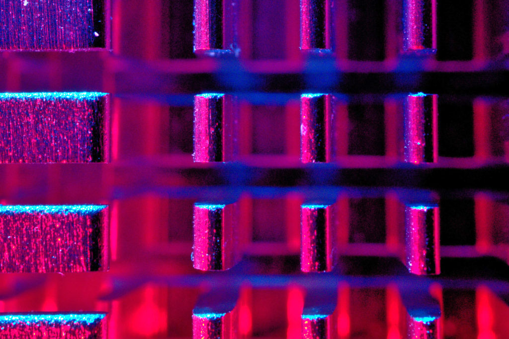 Image of inside of CPU lit with neon pink, blue and purple lighting for article is artificial intelligence better at marketing and copywriting than humans?