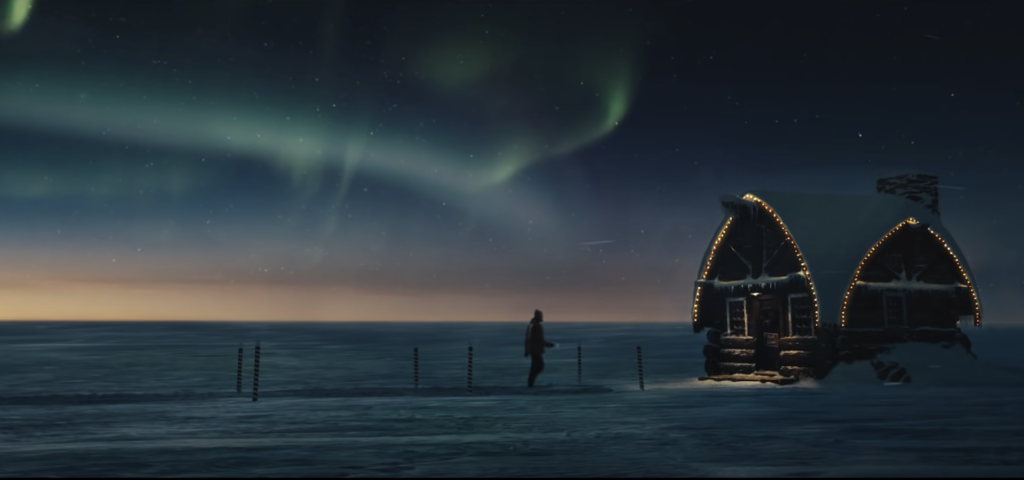 silhouette of man walking toward santa's home in the north pole with the northern lights in the sky in the background