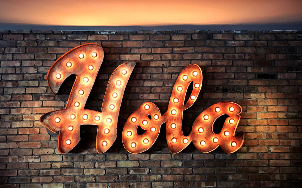 neon sign that says Hola - say hello the right way to new customers and users with this complete guide to onboarding