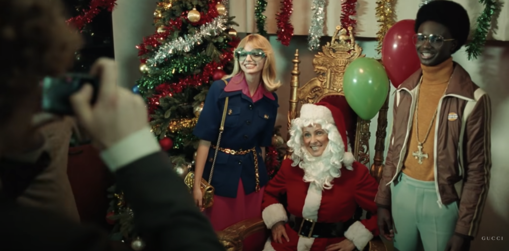 3 women smiling for a photo. One woman in the middle is seated and dressed as Santa. A still from the Gucci holiday marketing ad 2020