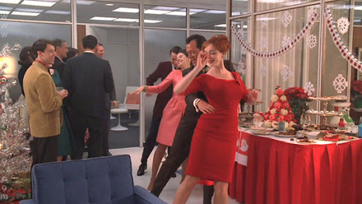 still from Mad Men with men and women at a holiday office party dancing in a conga line while others look on. Mad Men provides many classic examples of nostalgia marketing and advertising