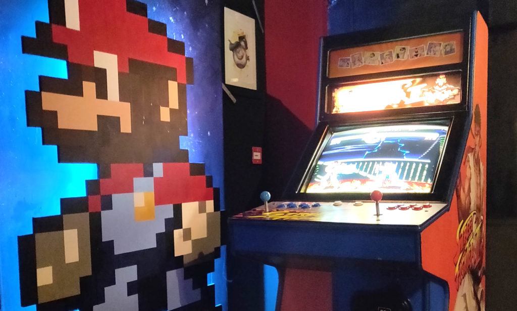 classic video game arcade machine with pixelated image of Mario from Super Mario Brothers. painted on the wall in the background - an example of nostalgia marketing, which was the biggest trend of 2020 during the pandemic and beyond
