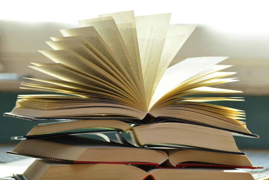 4 business and marketing books in a stack with the top book opened, pages fanned out