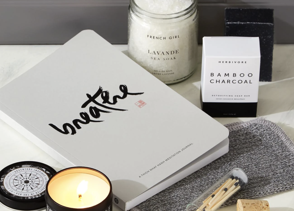 a notebook that says breathe on it next to a candle, box that says bamboo charcoal on it, and another jar of sea soak - a relaxing, pampering holiday gift for professionals, marketers and copywriters