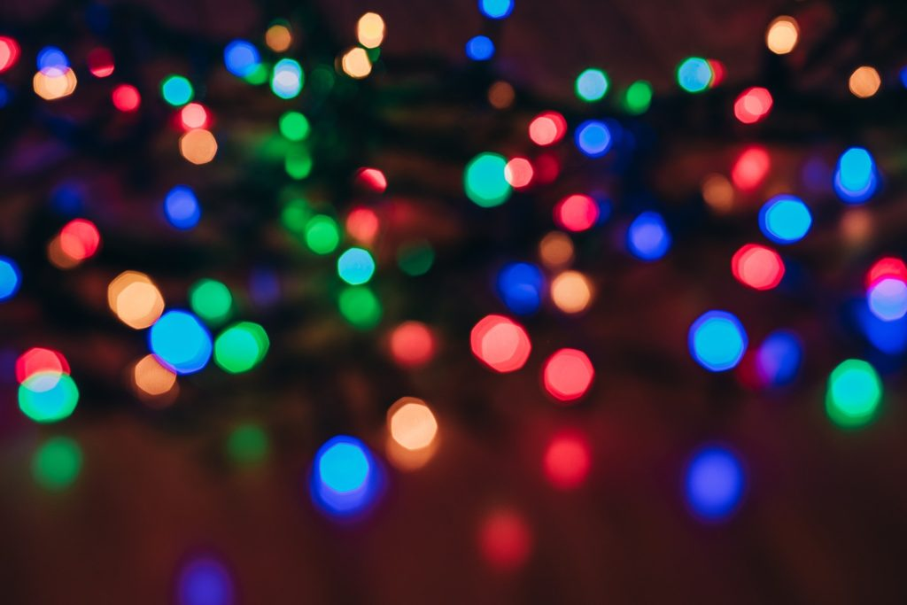 out of focus, multi-colored string lights on a dim background