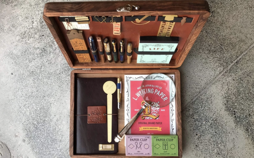 an open wooden box with numerous items inside that are for marketers and copywriters, including paper, magnifying glass, leather notebook, paper clips, pens, and more