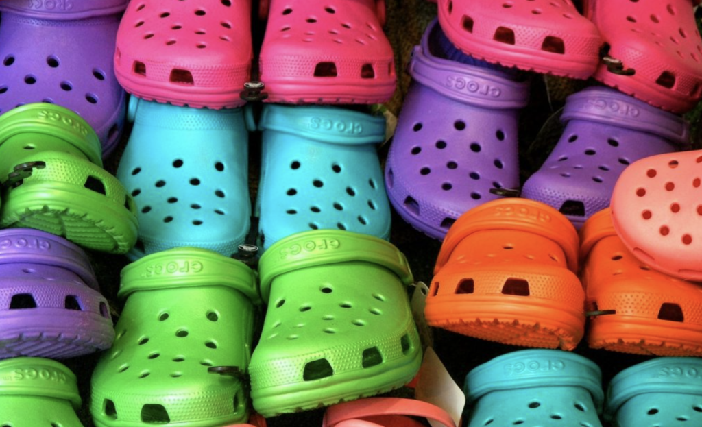 multicolored crocs shoes stacked in. rows - the crocs brand experienced success in 2020 due to innovative coronavirus marketing strategy and gen-z tiktok influencers