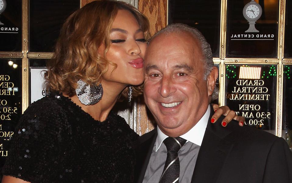 beyonce making a puckered lip face next to Sir Philip Green, chairman of arcadia group