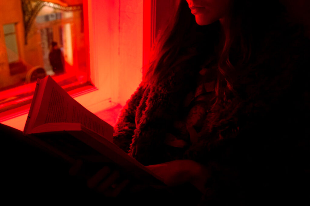 the best books to read in 2021, recommended for your reading list by business and marketing executives: image of someone reading by a window in shadow with red and orange neon light illuminating them through the window