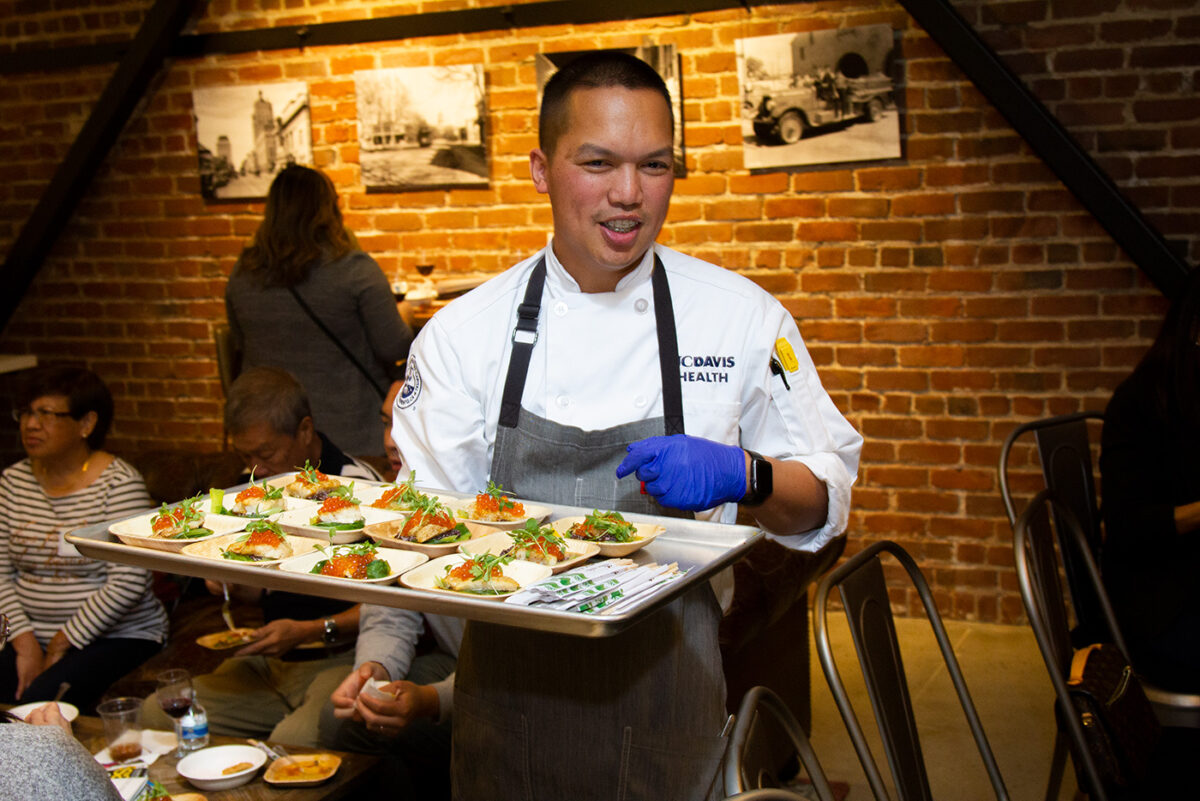 Jet Aguirre carries a tray of food during the AAJA Sacramento Chefs Showcase.