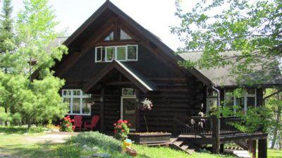 Main entry dark stained cedar log house