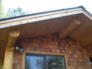 Log roof supportsStone and cedar Sauna building