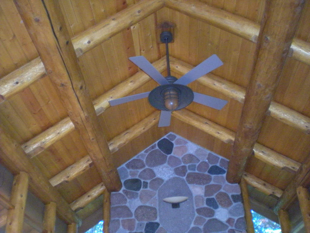 Ceiling fan against the log perlin and rafter roof
