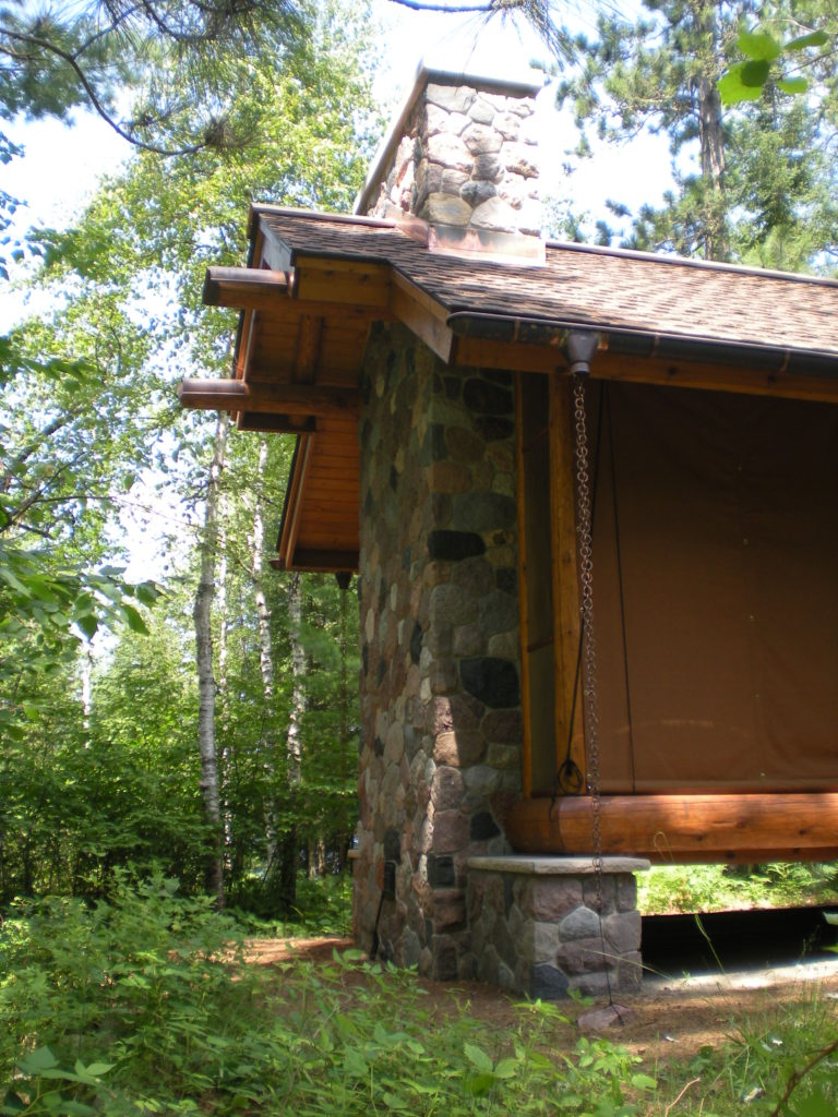Log gazebo stone fireplace and canvas screen covers