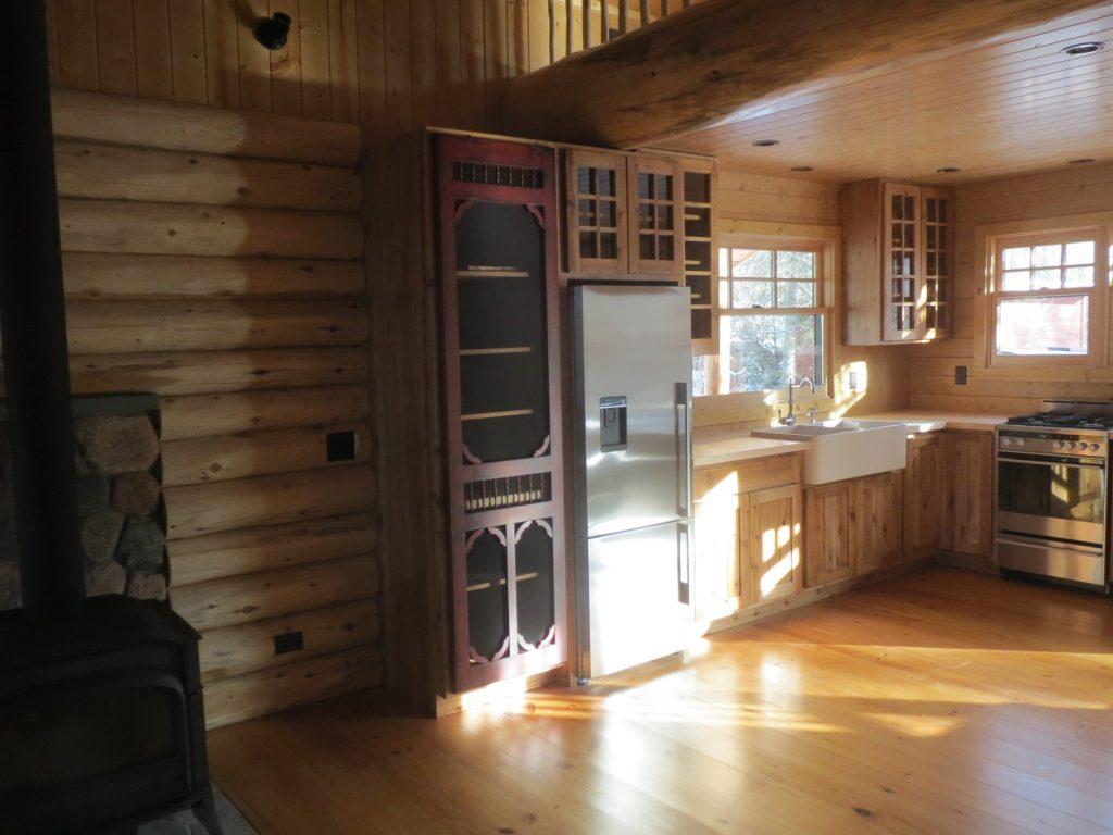 Kitchen area with custom built red screen cabinet door