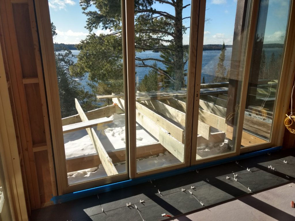 Tile starting in sunroom, and deck framing, view of the lake, Huisman Concepts custom home