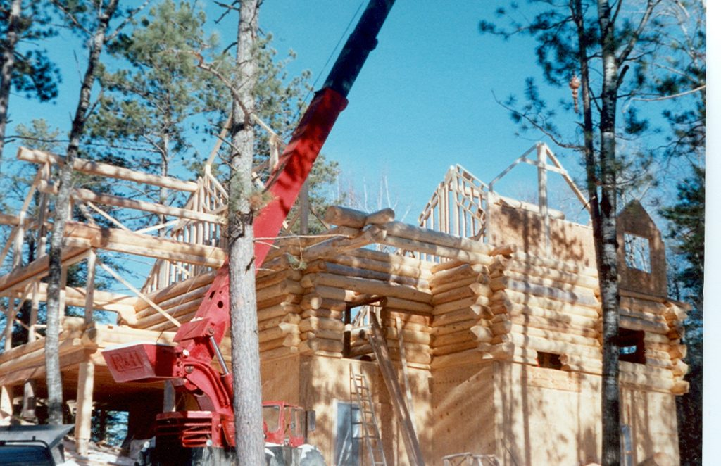 Log construction in progress, crane and roof beams