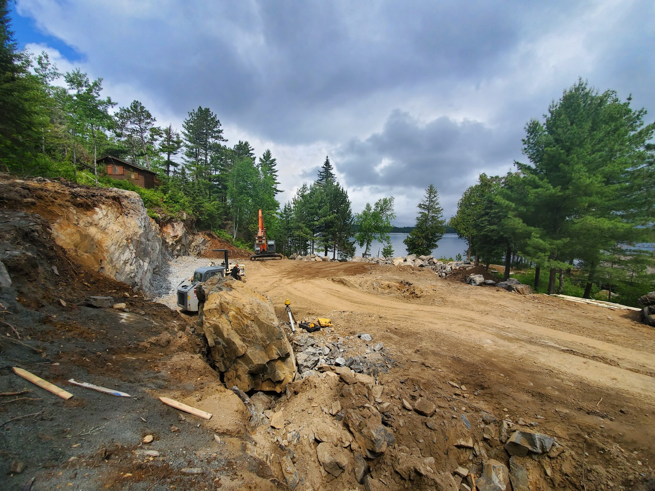 Blasting rock for new custom lake home by Huisman Concepts