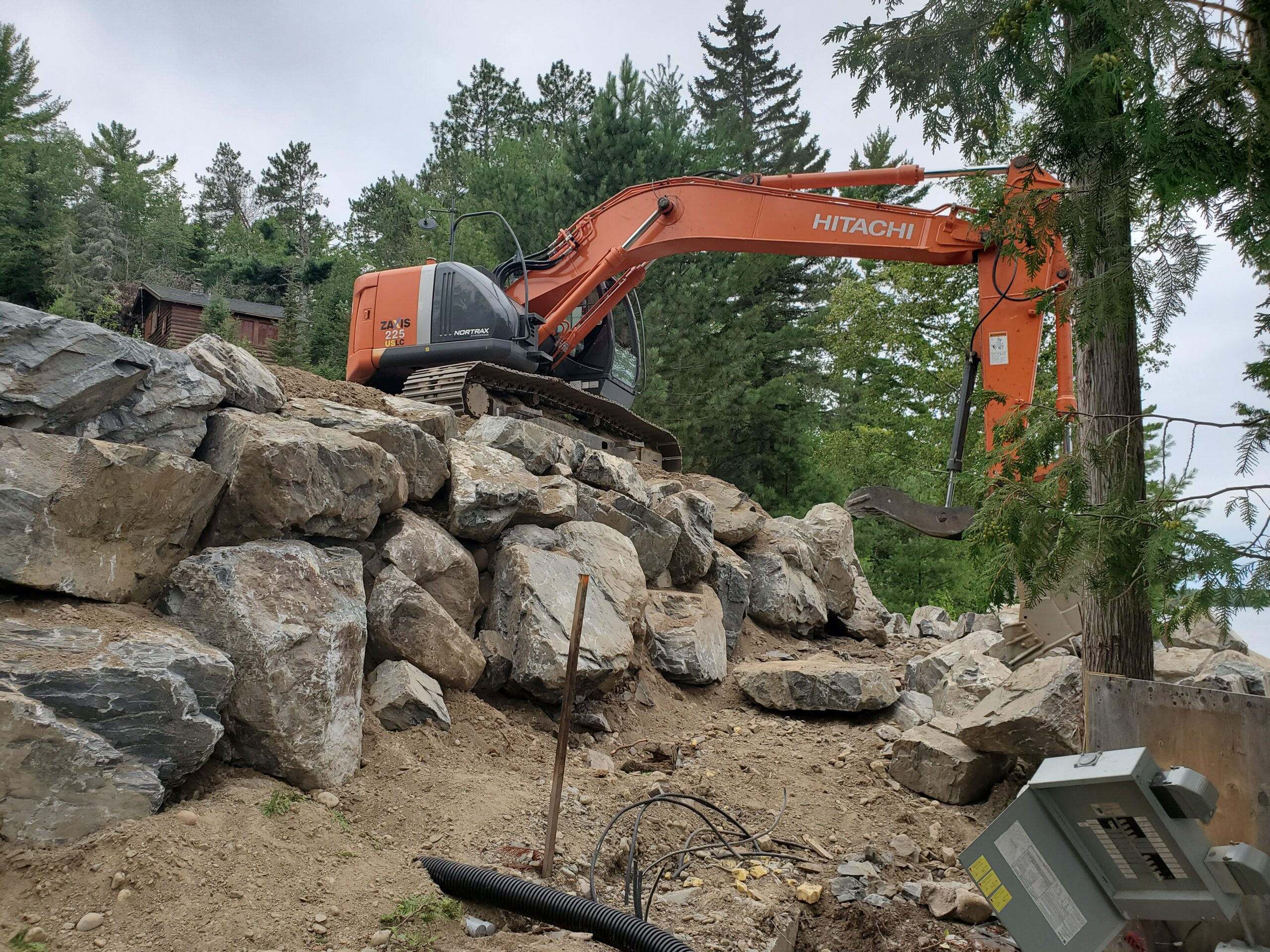 Retaining wall under way Retaining wall boulders, custom home by Huisman Concepts, Ely MN