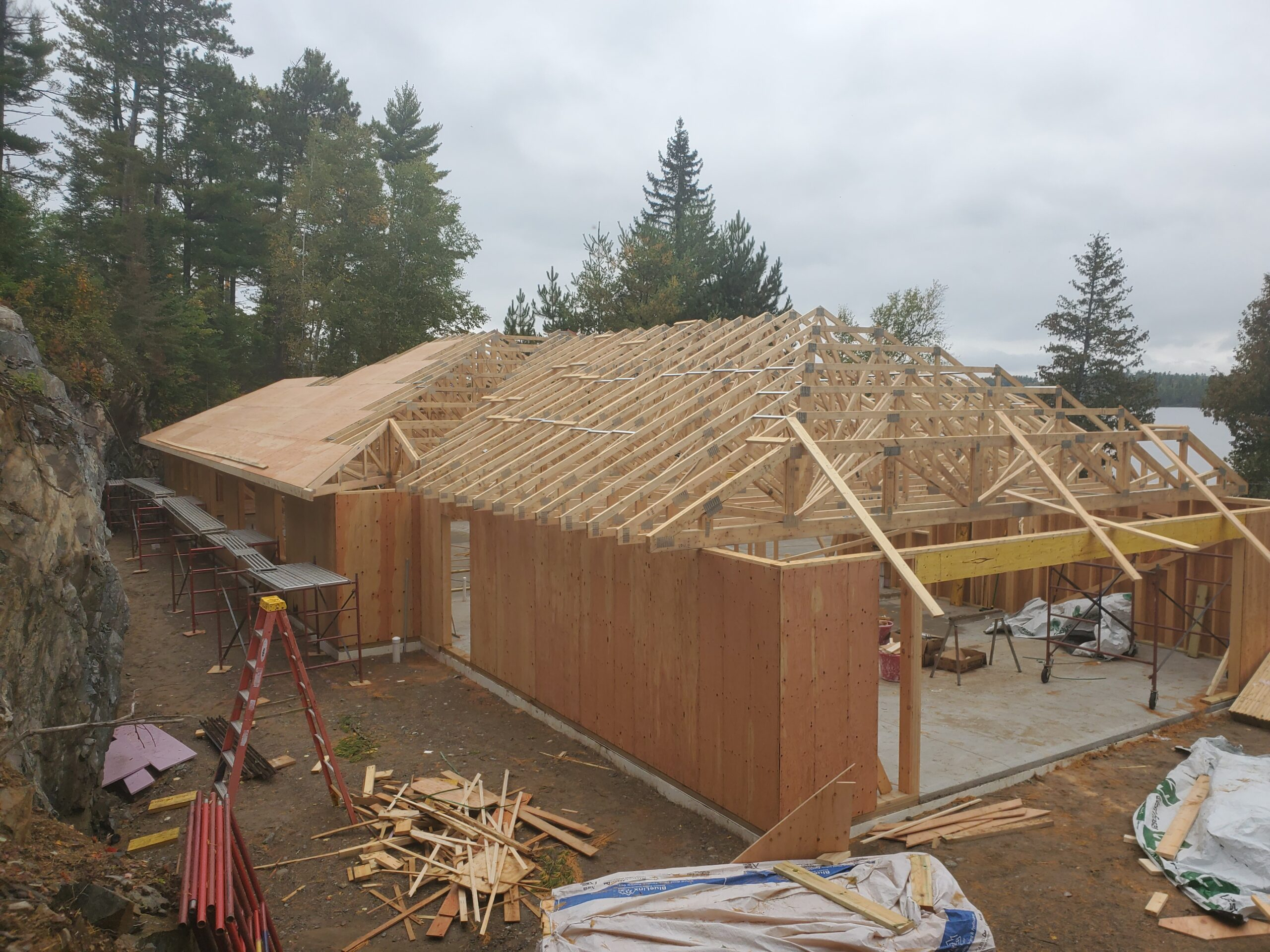 Trusses almost done, sheathing started, custom home Huisman Concepts