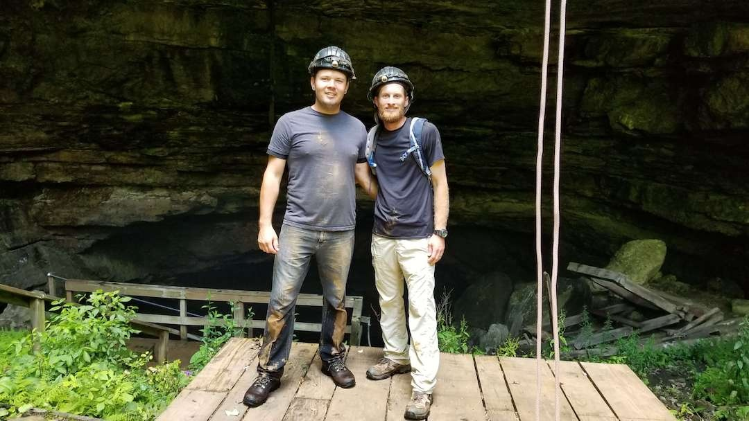 Two men muddy in front of Horse Cave