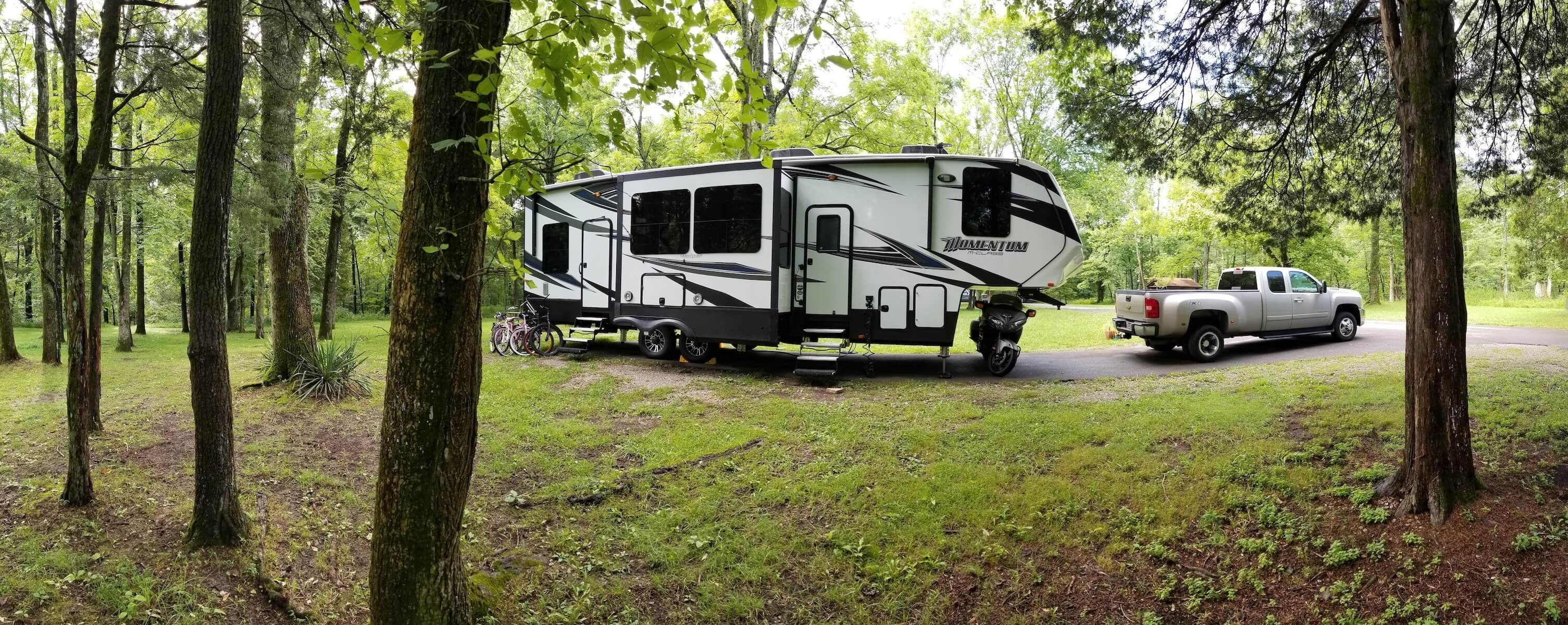 Grand Design Momentum Fifth Wheel with Dually Truck in Forest Campground