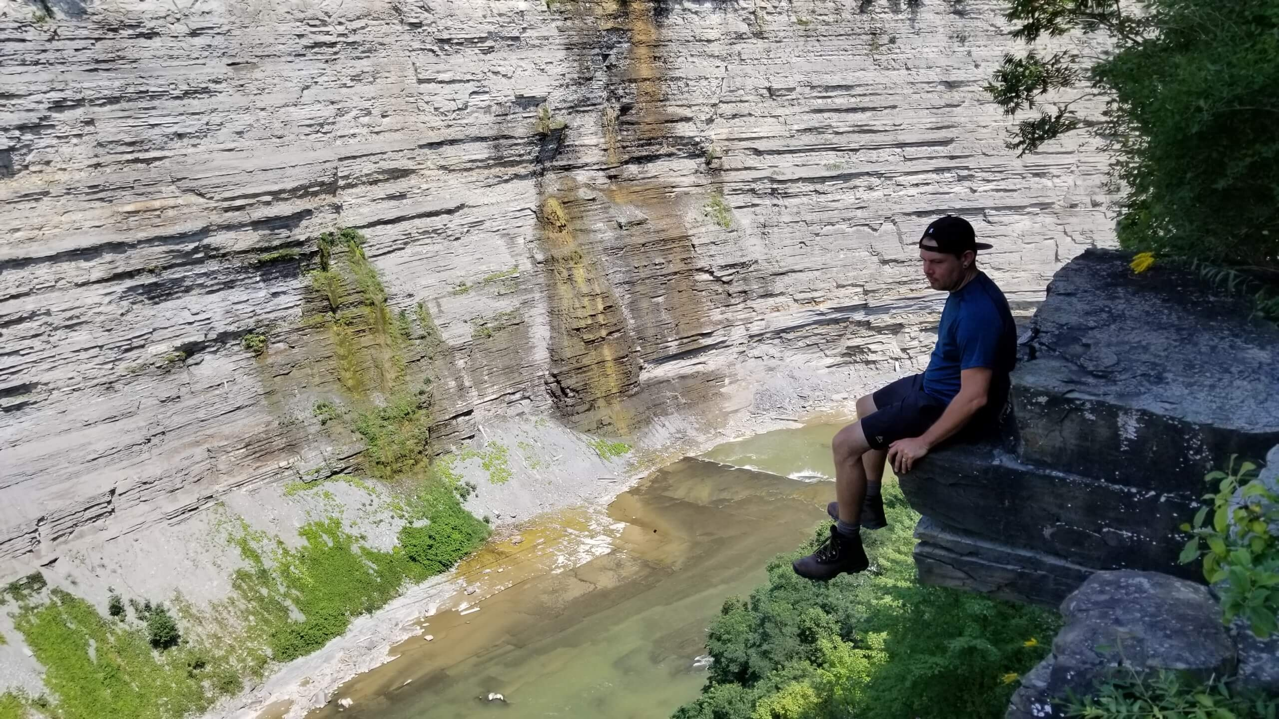 Man sitting on high Ledge over river