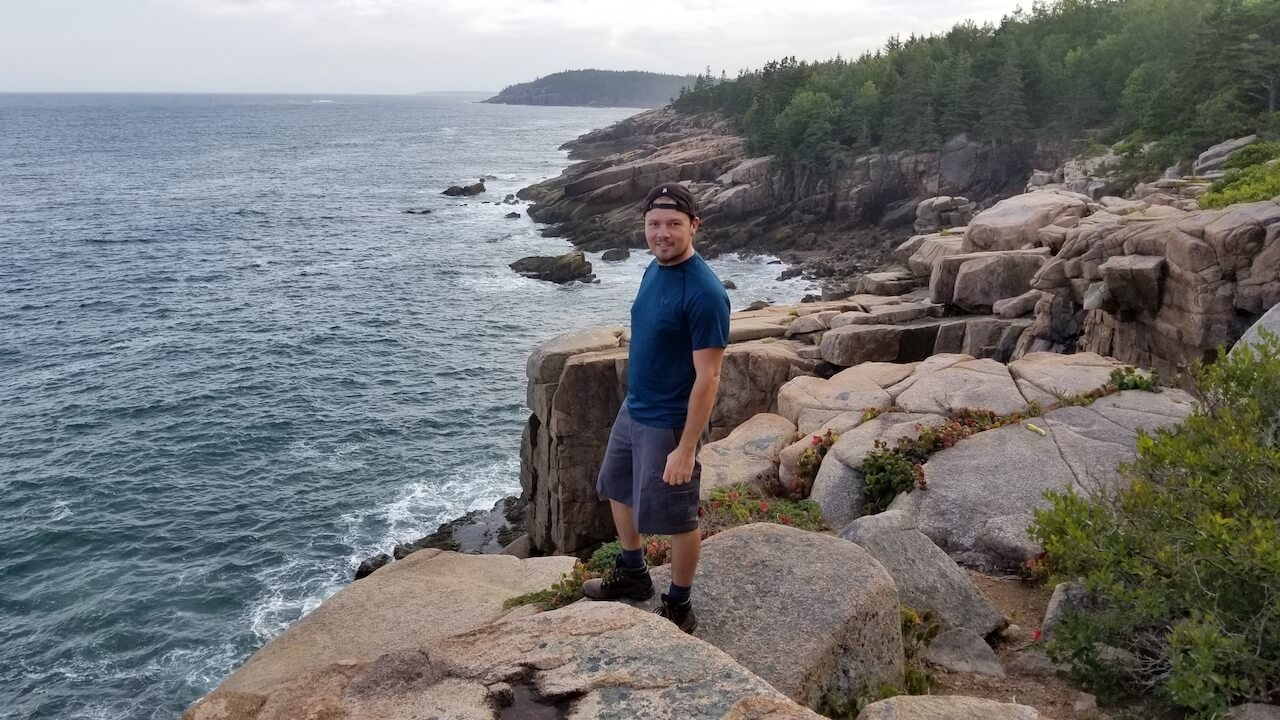 Dennis on rocky Maine cliff with ocean view in blue shirt