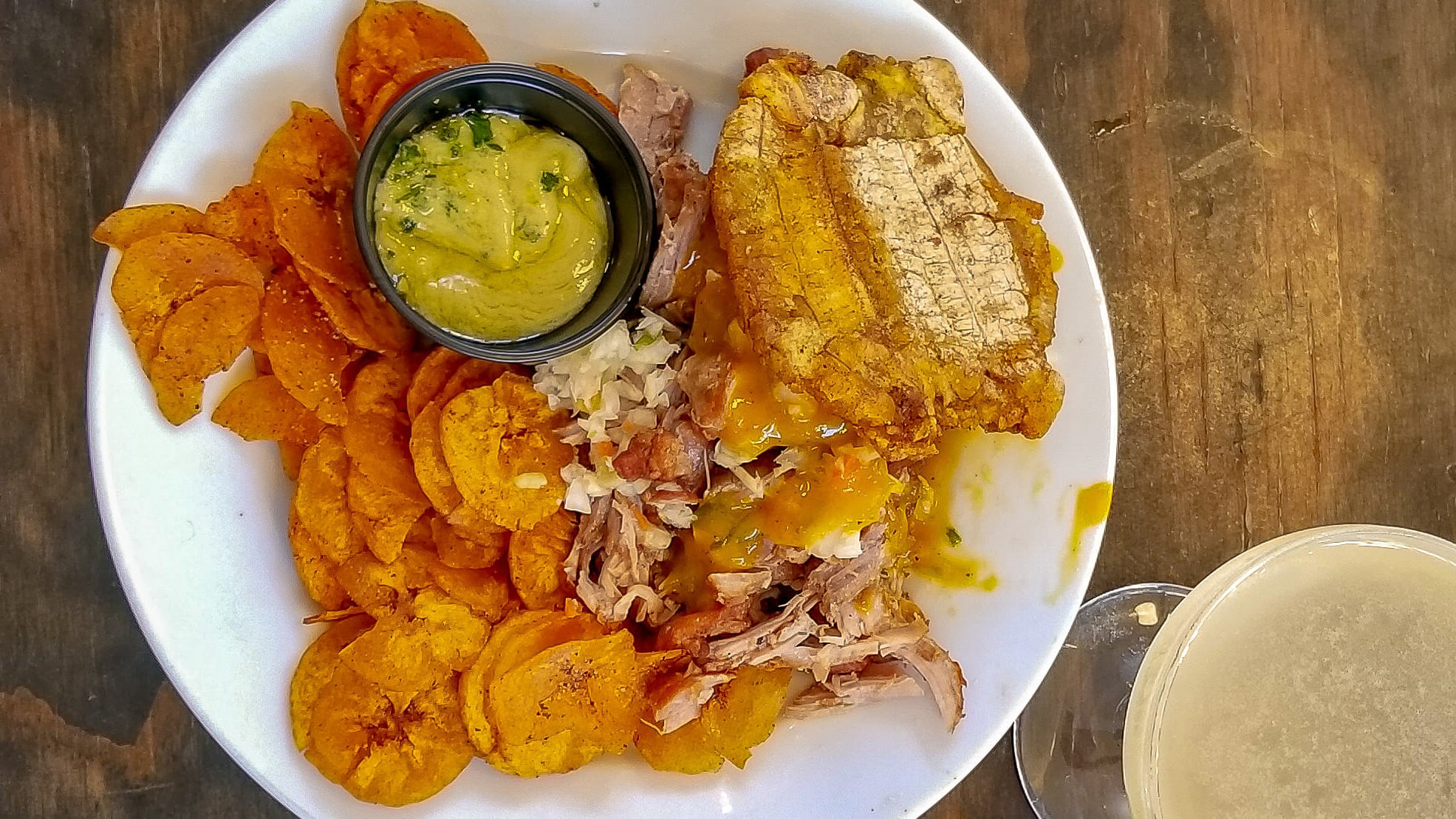 Plate with fried plantain chips with pork sandwich