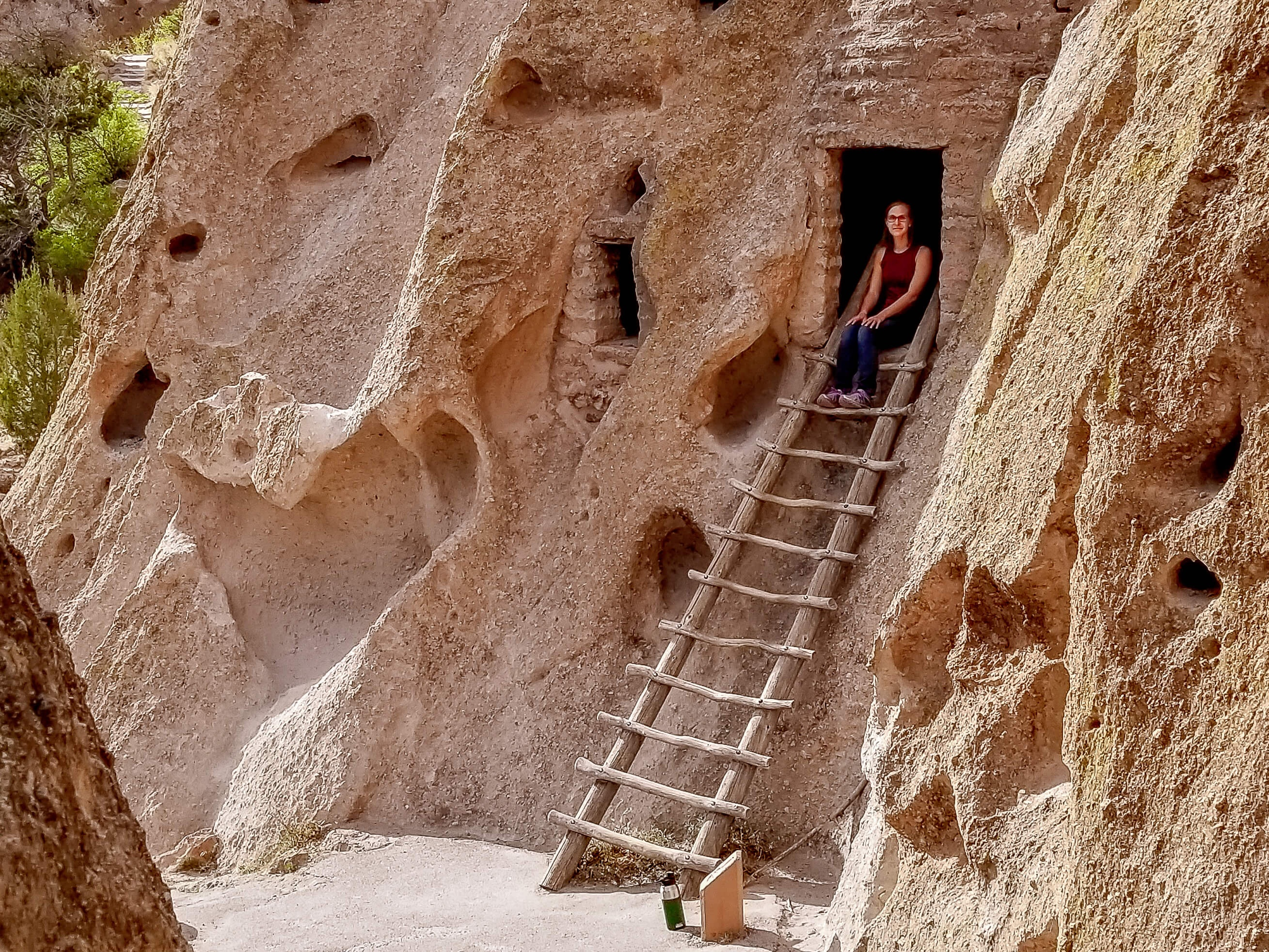 Liz sitting in cliff dwelling with stair Bandelier National Monument